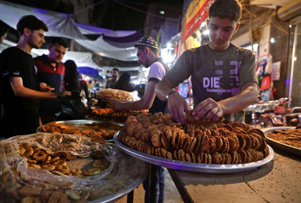 Men sell traditional sweets at a bakery in the town of Dana, in the northwestern Idlib province, as Muslims prepare for Eid al-Fitr. (AFP)