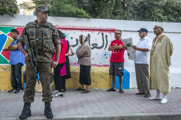 A member of the security force stands guard as voters queue outside a polling station during a 2019 parliamentary election in La Marsa, outside Tunis. (AP)