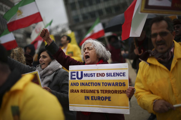 Activists of the National Council of Resistance of Iran shout slogans outside the European Council headquarters during a EU Foreign Ministers meeting in Brussels, Friday, Jan. 10, 2020. (AP)
