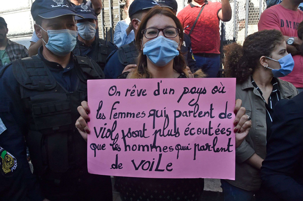 "An Algerian activist holds a placard reading in French ""we dream of a country where women who talk about rape are heard more than men who talk about veil"" during a rally in the capital Algiers on October 8. (AFP)"