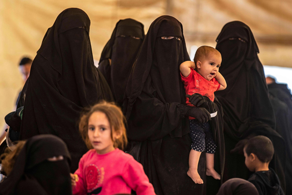 Women and children, suspected of being related to Islamic State (IS) group fighters, gather at the Kurdish-run al-Hol camp. (AFP)