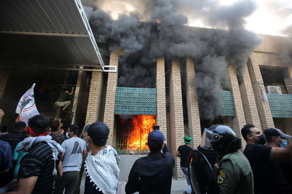 Iraqi demonstrators, supporters of the Hashed al Shaabi, burn down the Kurdish Democratic Party's headquarters in the capital Baghdad on October 17, 2020.(AFP)