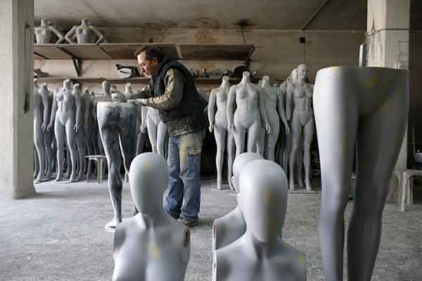 A worker in Ankara brushes dust off a mannequin part at a factory of Koray Vitrin Mankenleri, which exports to the Arab region. (REUTERS)