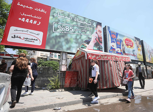 People walk underneath an advertising billboard of Syria's largest mobile operator Syriatel, owned by businessman Rami Makhlouf, in Damascus. (AFP)