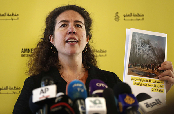 Heba Morayef, Amnesty International's Middle East Regional Director, holds a report at a press conference, in Beirut, Lebanon. (AP)