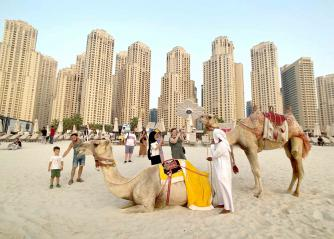 Tourists take photos with camels on the beach at Jumeirah Beach Residence in Dubai.(Reuters)
