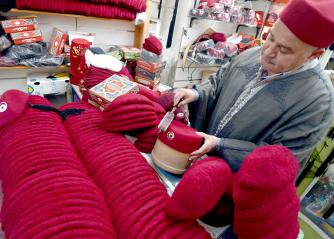 A Tunisian artisan displays traditional woven hats, known as chechias, at his shop in Tunis. (AFP)