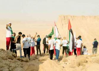 A group of Arab hikers carry their national flags in Saudi Arabia.(Al Arab)