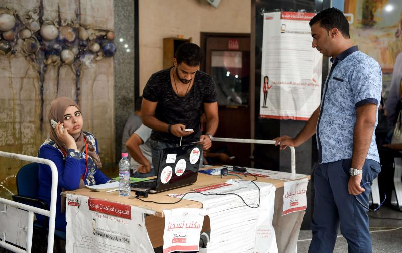 Getting out the vote. Employees of the ISIE election body work at an outreach booth at a shopping mall in Tunis, last August. (AFP)