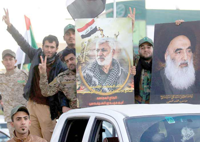 Members of Iraq's Popular Mobilisation Forces (PMF) flash the victory sign with portraits of Grand Ayatollah Ali al-Sistani (R) and PMF Chairman Abu Mahdi al-Muhandis, in Basra, on December 10. (AFP)