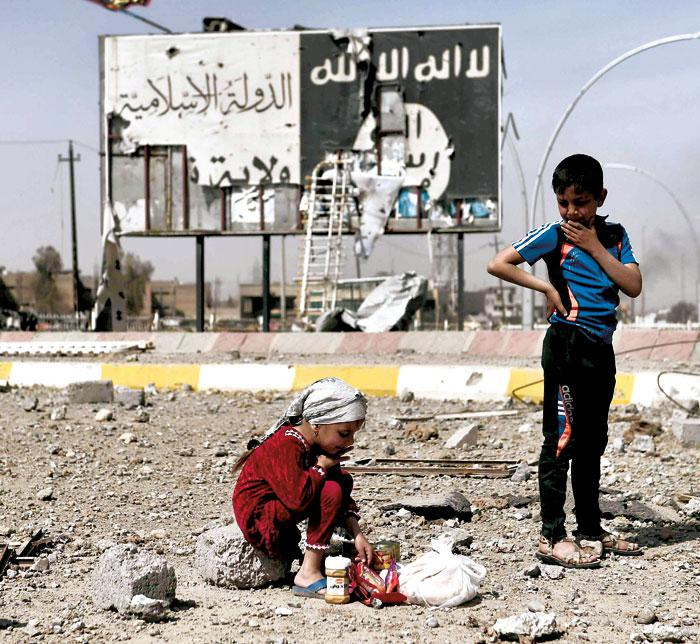 Iraqi children pose amid the rubble of a street in Mosul's Nablus neighbourhood in front of a billboard bearing the logo of ISIS. (AFP)