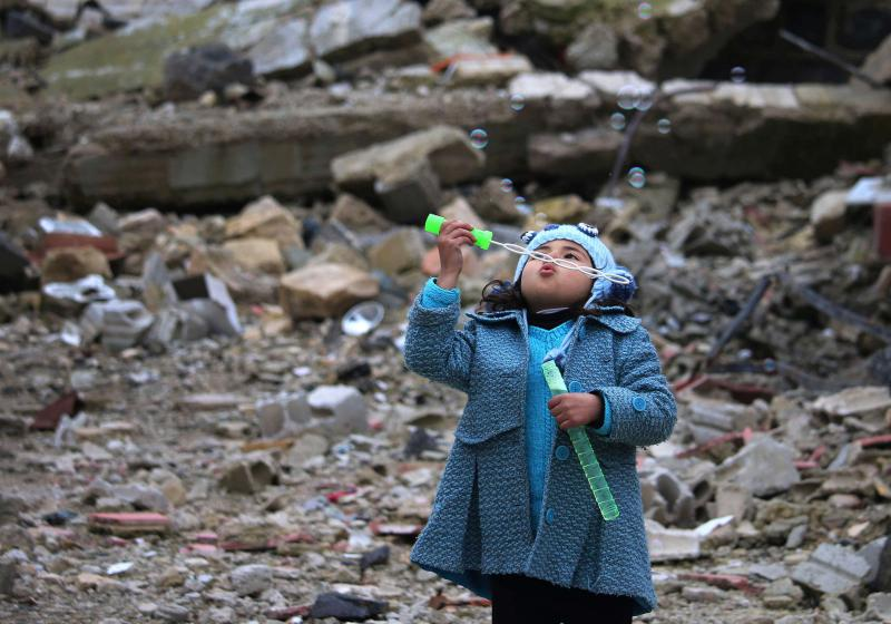 Blowing the pain away. A Syrian girl blows bubbles amid the rubble of destroyed buildings in Daraa in southern Syria. (AFP)