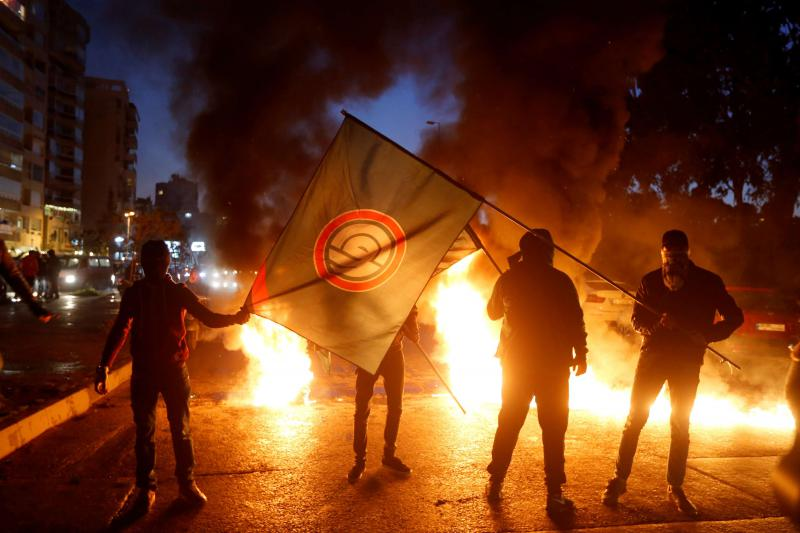 Heated dissonance. Supporters of Amal movement hold the party's flag near burning tires in Beirut, on January 29. (Reuters)