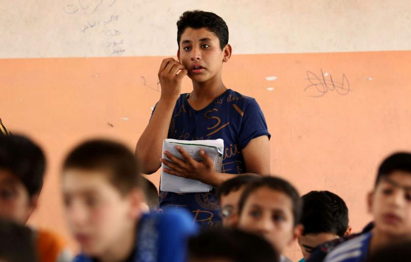Iraqi boys attend a class at a school in west Mosul. (AFP)
