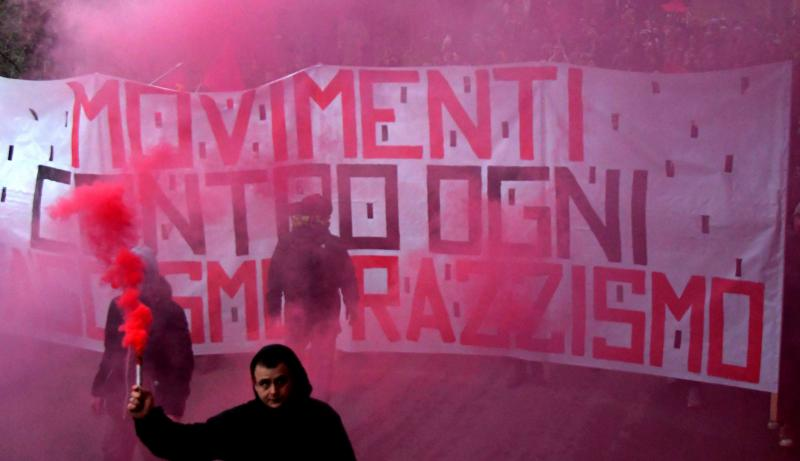"A man holds a flare in front of a banner reading ""Movements against fascism and racism"" during an anti-racism demonstration in the Italian town of Macerata, on February 10. (AFP)"