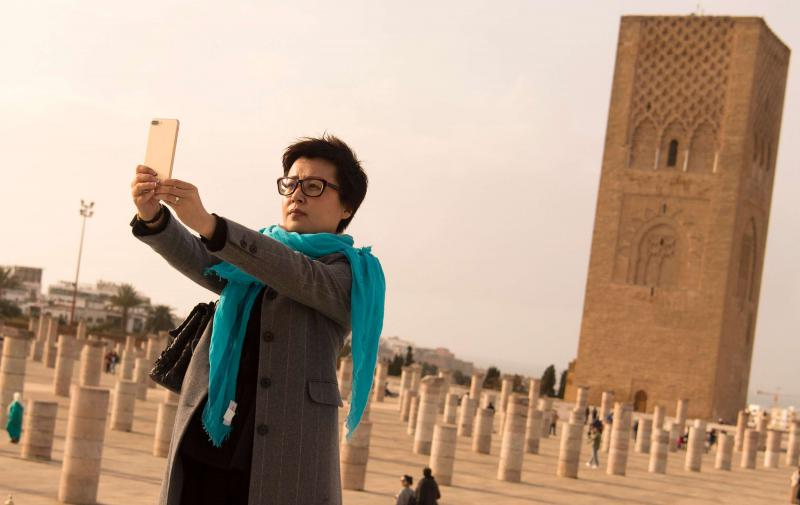An Asian tourist takes a selfie in front of the Hassan Tower in Rabat. (AFP)