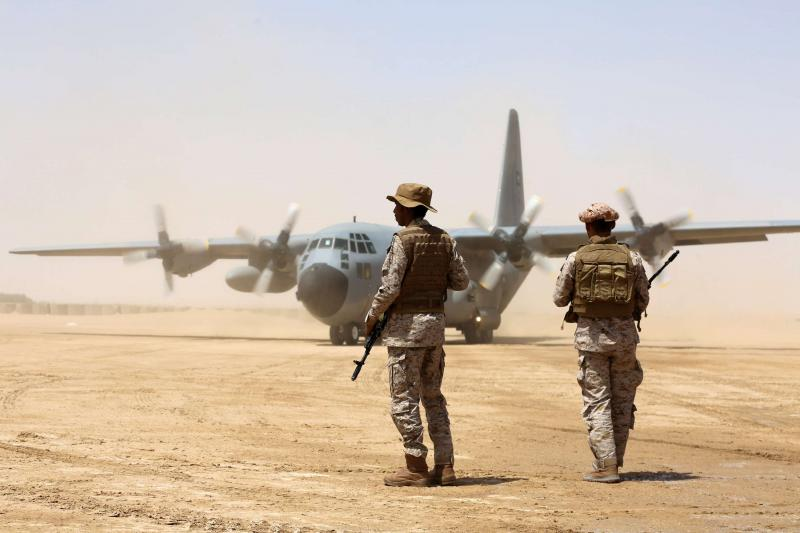 Soldiers stand guard before aid supplies are unloaded from a Saudi air force cargo plane at an airfield in Yemen's central province of Marib, on March 12. (AFP)