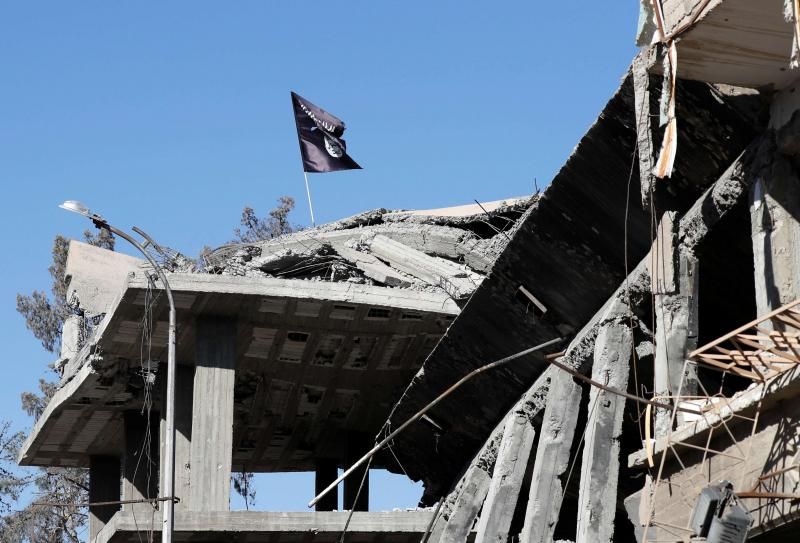 An ISIS flag flutters above a destroyed house near the Clock Square in Raqqa, last October 18.  (Reuters)