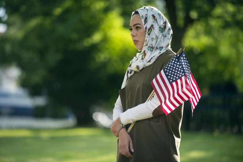 An Arab woman holds American flags in Flint, Michigan, last June.  (AP)