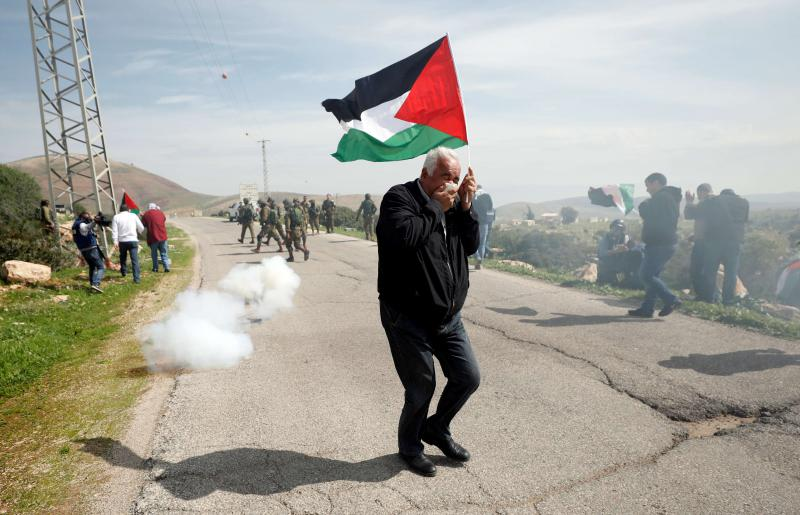 A Palestinian demonstrator reacts as tear gas is fired by Israeli troops during a protest against Jewish settlements near Tubas in the occupied West Bank, February 25.   	 (Reuters)