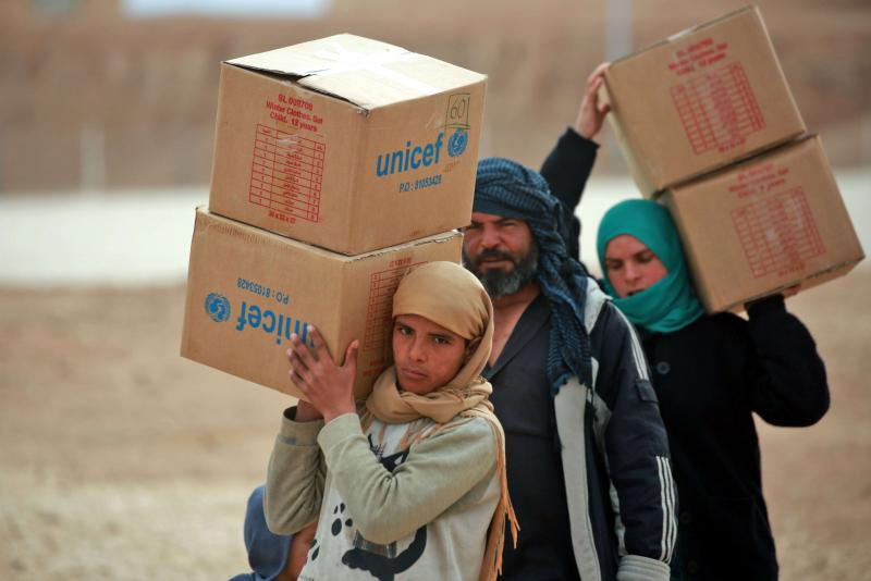 Displaced Syrians carry boxes of humanitarian aid supplied by UNICEF at a refugee camp in Syria's northeastern Hassakeh province, on February 26. (AFP)