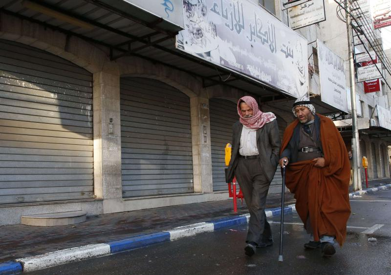 Worsening toll. Palestinian men walk past closed shops in the West Bank city of Hebron, last December. (AFP)