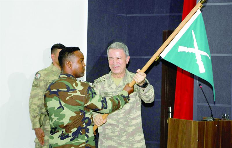 Turkish Chief of Staff General Hulusi Akar (R) hands a flag to a Somali soldier at the new Turkish-Somali military training centre in Mogadishu, last September.  (AP)