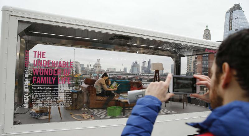 A tourist takes a picture of a woman and child reading a book as they sit inside a perspex container and go about their normal family life backdropped by the River Thames and St Paul's Cathedral, centre, in the City of London, Friday, March 9, 2018. Amnesty International UK is staging the living installation over Mother's Day weekend, entitled 'The Undeniable Wonder of Family Life', celebrating the joy of spending time with family and highlighting the importance of reuniting refugee families.(AP Photo/Alast