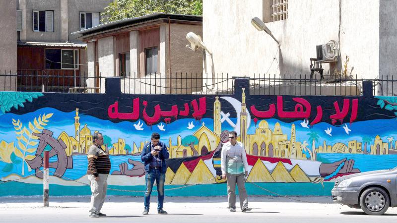 "Egyptians walk past a mural with a caption in Arabic that reads ""Terrorism has no religion.""  (AFP)"