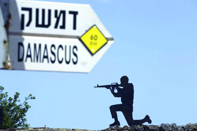 A mock road sign for Damascus and a cutout of a soldier on display in an old outpost in the Israeli controlled Golan Heights, on May 10.    (AP)