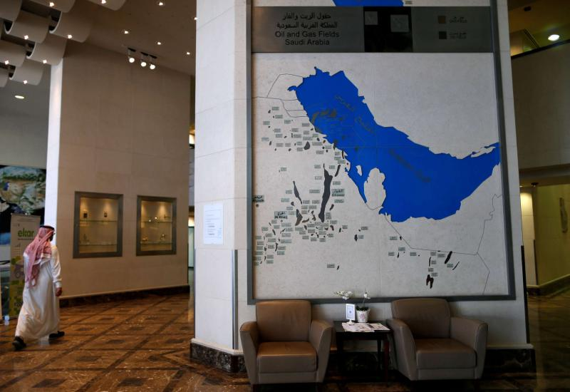 An employee in Aramco's headquarters in Dhahran walks past a giant map showing the location of oil and gas fields in Saudi Arabia. (Reuters)