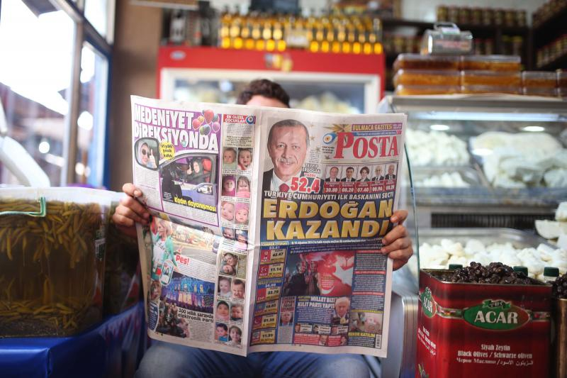 A shopowner reads a newspaper, featuring coverage of the election results in the mainly-Kurdish city of Diyarbakir in southeastern Turkey, on June 25. (AP)