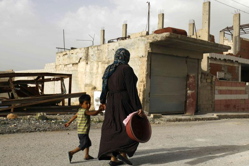 A Syrian woman walks past destroyed buildings in Kobane, on May 27. (AFP)