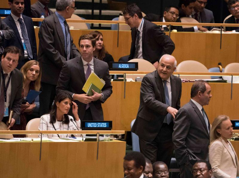 Palestinian Ambassador to the United Nations Riyad Mansour passes by US Ambassador Nikki Haley during voting to condemn Israeli actions in Gaza, at the General Assembly, in New York, on June 13. (AFP)