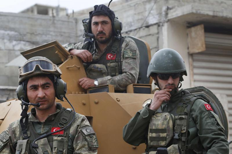 Turkish soldiers atop an armoured personnel carrier secure the streets of Afrin during a Turkish government-organised media tour. (AP)
