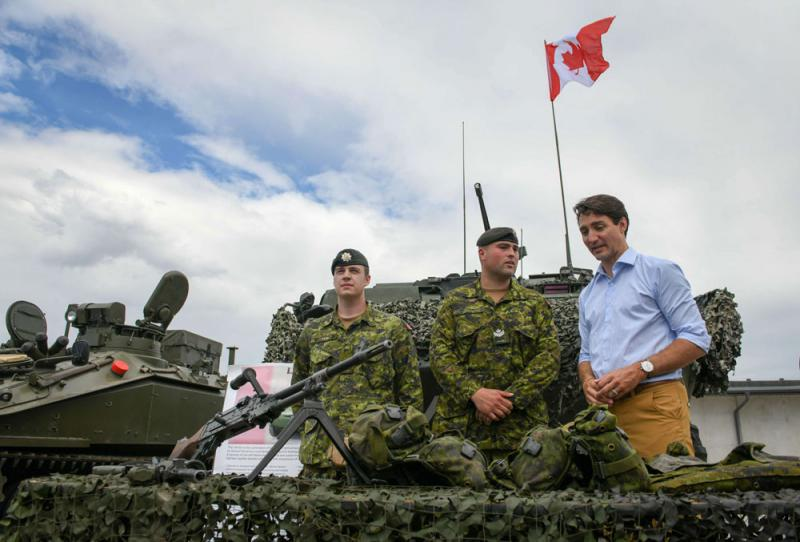 Canada's Prime Minister Justin Trudeau looks at military equipment as he meets with NATO battle group troops in Adazi, Latvia, on July 10. (AFP)