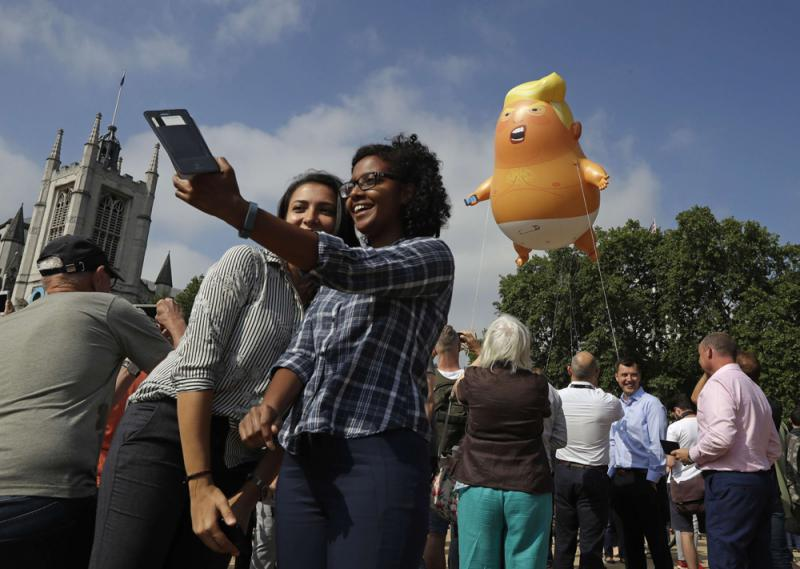 People take photos of a six-meter high cartoon baby blimp of US President Donald Trump is flown as a protest against his visit, in London, on July 13. (AP)