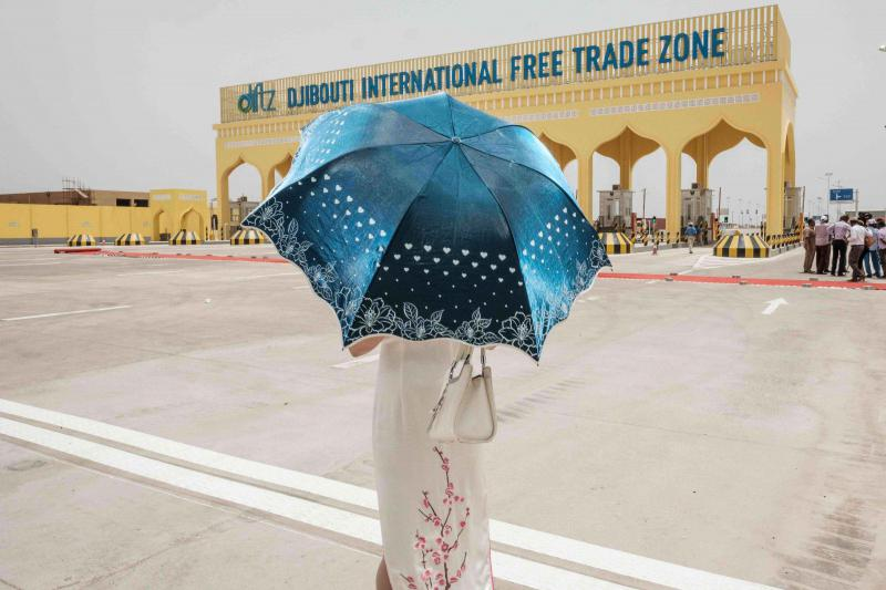 Security umbrellas. A Chinese woman uses a parasol in front of the main gate of Djibouti International Free Trade Zone (DIFTZ) after the inauguration ceremony in Djibouti, last July. (AFP)
