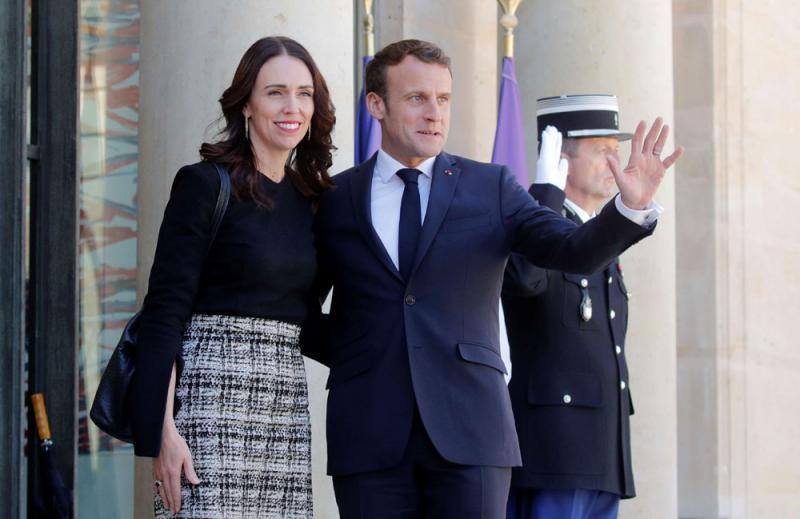 French President Emmanuel Macron waves next to New Zealand's Prime Minister Jacinda Ardern, at the Elysee Palace in Paris, May 15. (Reuters)