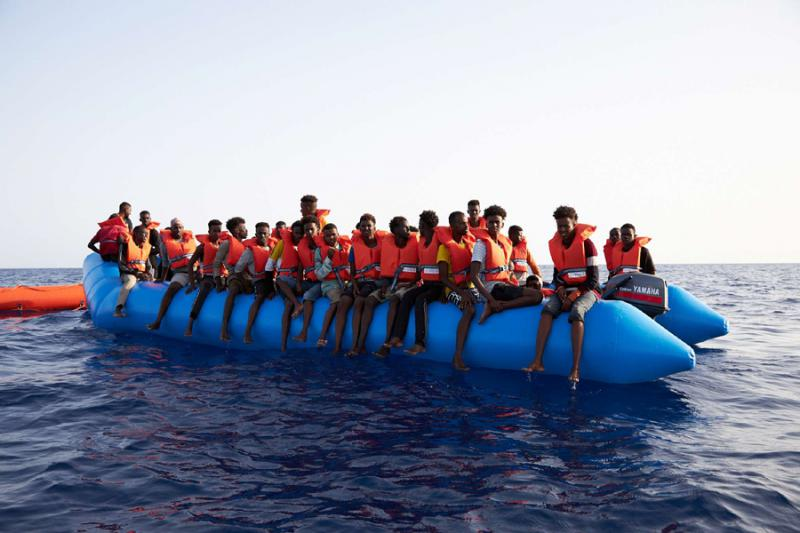 A blue inflatable boat carrying 65 people, about 34 miles from the Libyan coast, July 5. (Sea-eye/Social Media via Reuters)