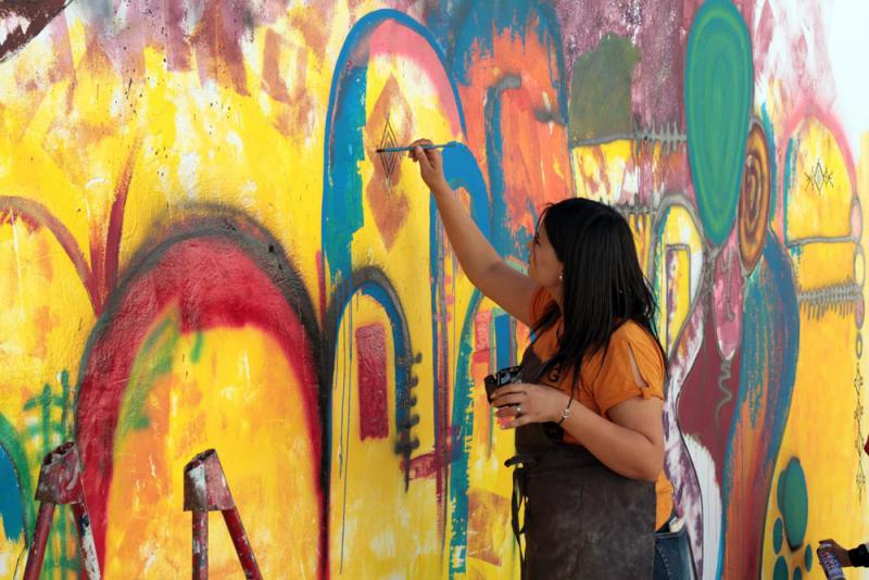Colours invading the city. An artist works on a mural in Tataouine.         (JAAC)