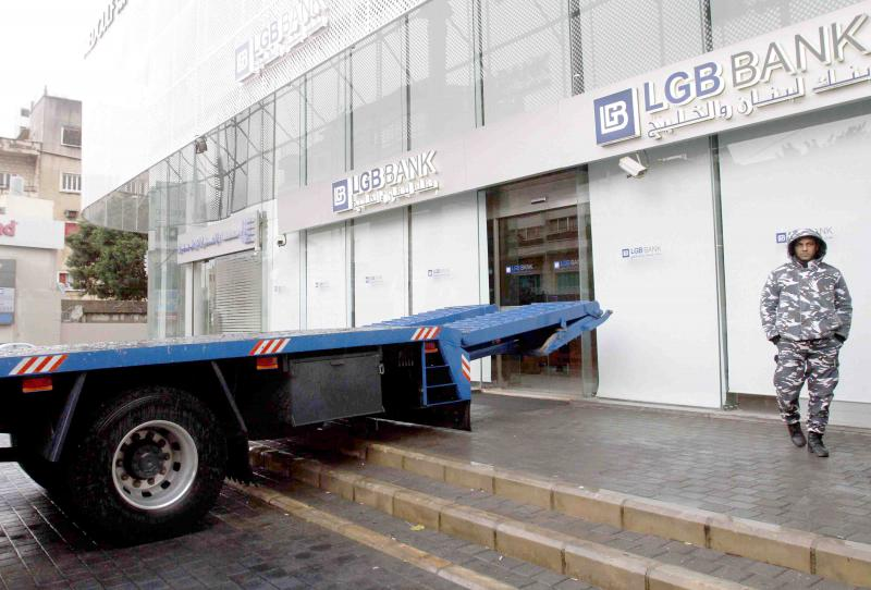A flatbed truck, placed by an angry Lebanese client, blocks the entrance to his bank branch in the southern Lebanese city of Sidon, January 4.(AFP)