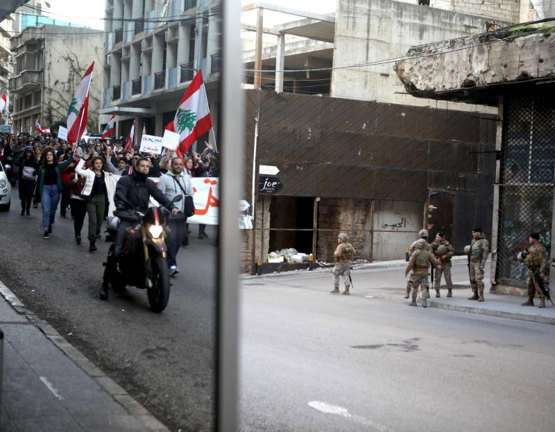 An image reflected in a shop window shows Lebanese  anti-government protesters marching during a demonstration as army soldiers look on from across the street in Beirut,  January 25. (AFP)