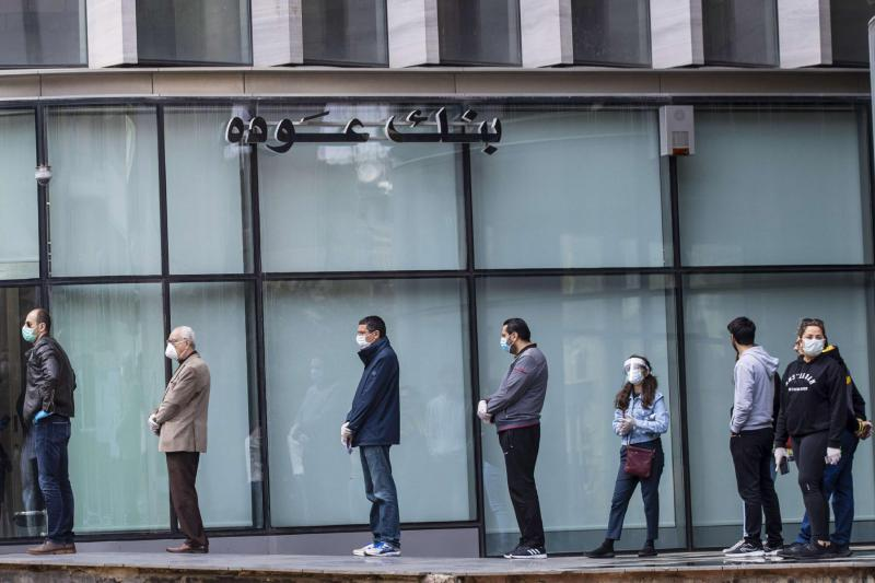 Clients wearing protective masks line up to use ATM machines outside a closed bank in Beirut, Lebanon. (AP)