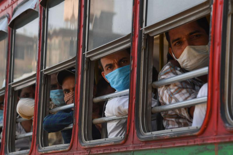 Migrant workers sit in a bus outside a train terminus while waiting for their train during a nationwide lockdown to fight the spread of the COVID-19 coronavirus, in Mumbai on May 8. (AFP)