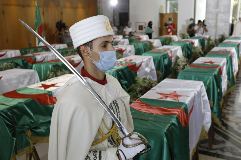 An Algerian soldier guards the remains of 24 Algerian resistance fighters at the Moufdi-Zakaria culture palace in Algiers, after their repatriation from France, July, 3. (AFP)