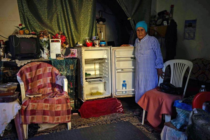 A Lebanese woman stands next to her empty refrigerator in her apartment in the port city of Tripoli. (AFP)