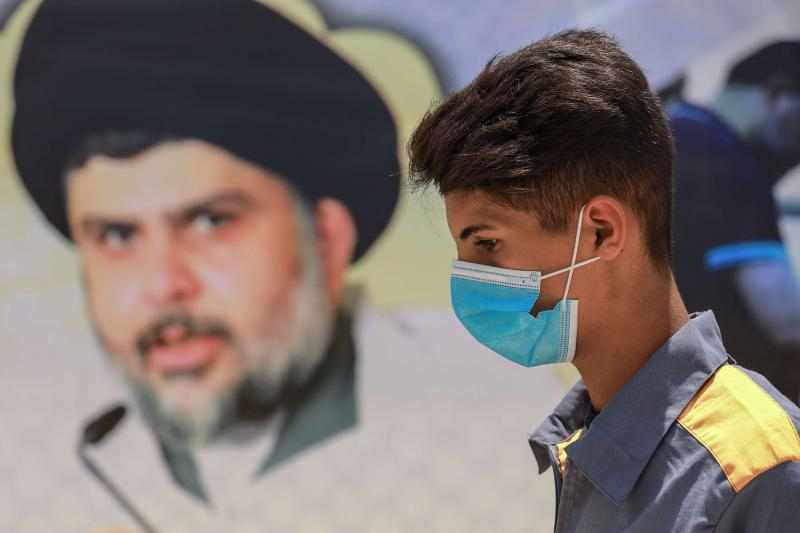 An Iraqi worker walks past a poster bearing the picture of Shia cleric Muqtada al-Sadr, at the premises of Al-Ataa hospital, in Sadr City, Baghdad. (DPA)