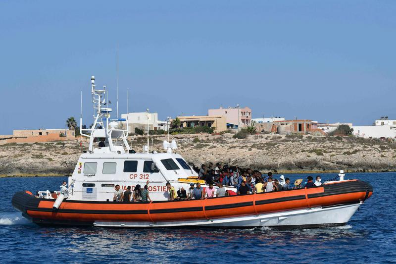 Migrants from Tunisia and Lybia arrive onboard of an Italian Guardia Costiera (Coast Guard) boat in the Italian island of Lampedusa on August 1. (AFP)