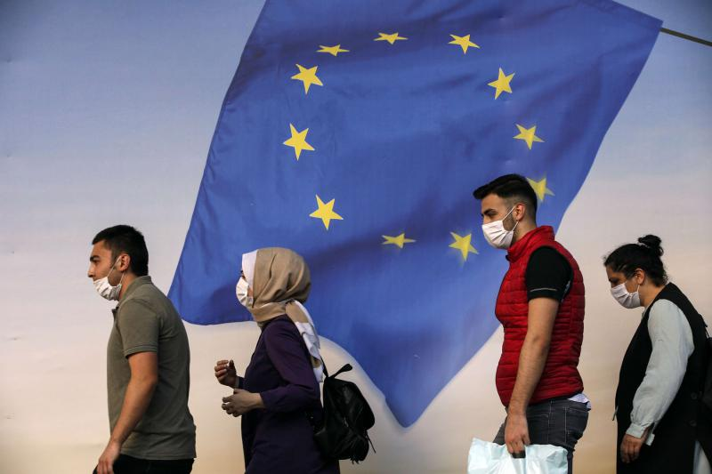 A file photo shows people in Istanbul, Turkey, walking past a poster of a European Union flag. (AP)